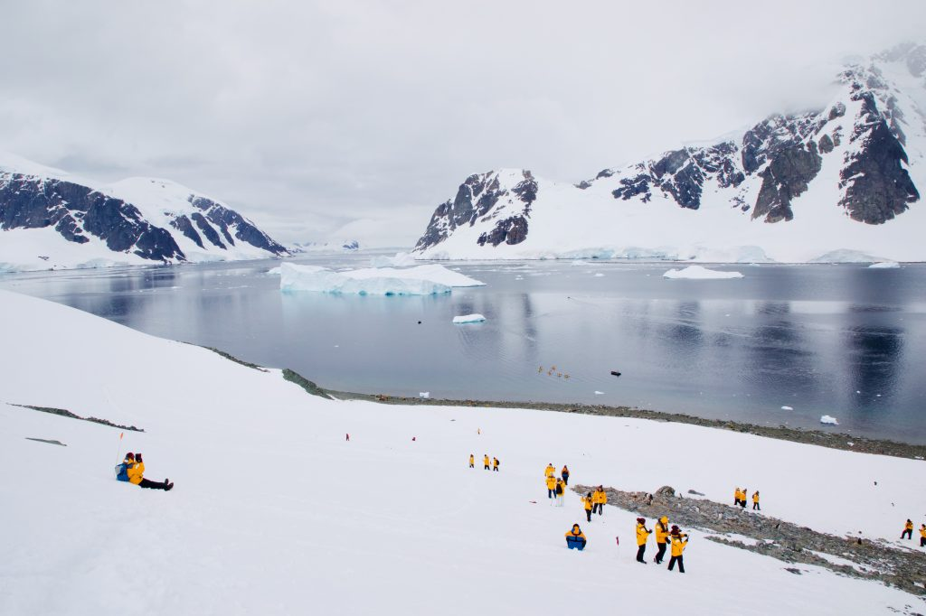 Photo of people in yellow jackets in Antarctica with snowcapped mountains and the ocean is in the background and light gray skies