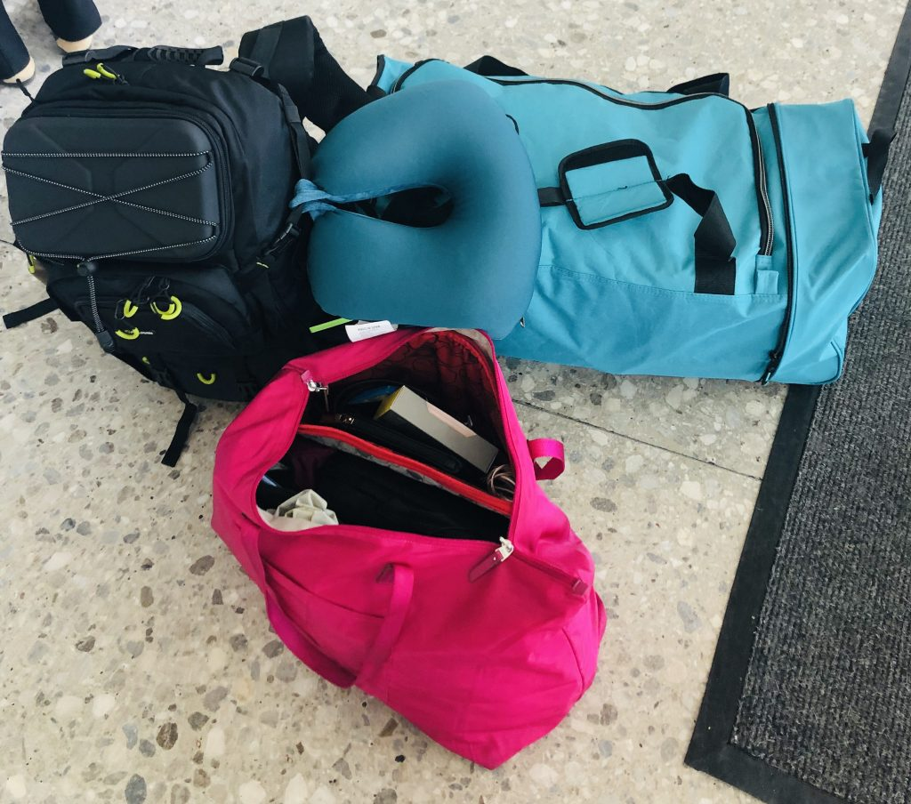 photo of one black camera book bag, one turquoise duffle bag and a hot pink carry-on tote