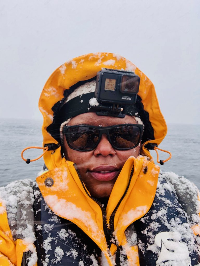 Close up of African American woman with yellow coat and GoPro on her head with snow on her while snow flakes are visible on the photo.