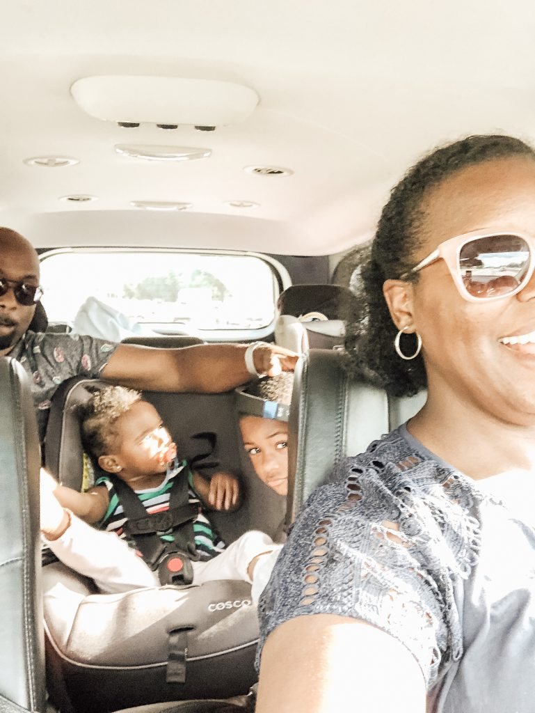 Family of four inside of a car on a road trip.